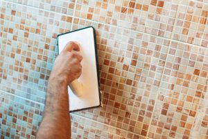 Unrecognizable male craftsperson applying grout on modern mosaic ceramic tiles in kitchen or bathroom. Adult Caucasian man.